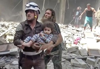 339eb91200000578-0-a_civil_defence_worker_carries_a_child_through_the_rubble_strewn-a-12_1461888901833